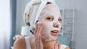 Glimlachende vrouw die verjongend kosmetisch wit weefselmasker op gezicht bevestigen stock video