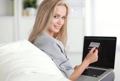 Glimlachende vrouw die voor online aankoop met kaart betalen stock afbeelding
