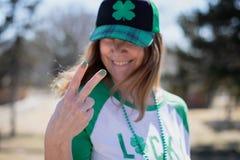 Glimlachende vrouw die vredesteken geven bij St Patricks Dagviering royalty-vrije stock foto's