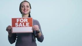 Glimlachende vrouw die witte tekenraad voor verkoop houden stock footage