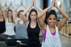 Glimlachende vrouw die yoga in gymnastiek doen stock foto's