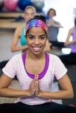 Glimlachende vrouw die yoga in gymnastiek doen royalty-vrije stock afbeelding