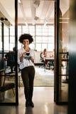 Glimlachende vrouw die zich in bureaudeuropening bevinden met koffie Stock Foto