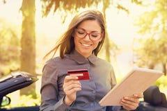 Glimlachende vrouw die zich door haar auto bevinden die online betaling op haar tabletcomputer buiten verrichten op een de zomerd stock fotografie