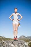 Glimlachende vrouw die zich op rots met handen op heupen bevinden stock foto