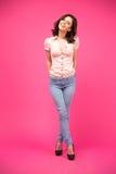 Glimlachende vrouw die zich over roze achtergrond bevinden Royalty-vrije Stock Foto