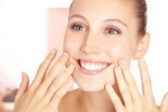 Glimlachende vrouw die zuivere huid voelt stock afbeelding