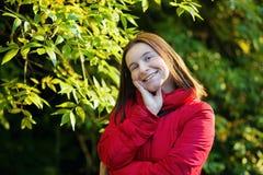 Glimlachende vrouw in een rood jasje Stock Afbeeldingen