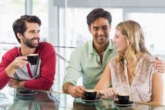 Glimlachende vrouw en twee mannen die kop van koffie hebben Stock Afbeeldingen