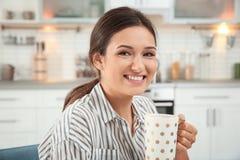Glimlachende vrouw in gestreepte blouse het drinken thee Royalty-vrije Stock Afbeeldingen