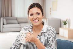 Glimlachende vrouw in gestreepte blouse het drinken thee Stock Afbeeldingen