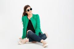 Glimlachende vrouw in groen jasje, gescheurde jeans en zonnebril royalty-vrije stock fotografie