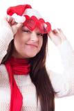 Glimlachende vrouw in Kerstmanhoed die hart-vormige glazen opheffen Royalty-vrije Stock Afbeeldingen