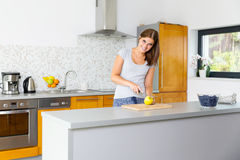 Glimlachende vrouw in keuken snijdende appel Royalty-vrije Stock Foto's