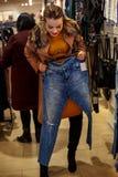 Glimlachende vrouw in kledingsopslag het winkelen Stock Afbeelding