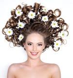 Glimlachende vrouw met bloemen in haar Royalty-vrije Stock Foto's