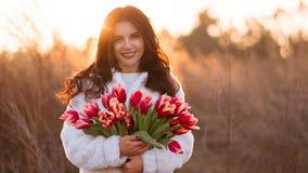 Glimlachende vrouw met bos van bloemen stock afbeeldingen