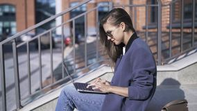 Glimlachende vrouw met buiten laptop op treden stock videobeelden