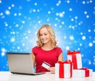 Glimlachende vrouw met creditcard en laptop Stock Foto's