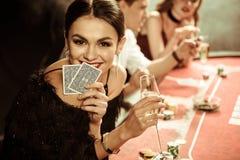 Glimlachende vrouw met drank en kaarten die pook spelen stock fotografie
