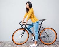 Glimlachende vrouw met fiets Stock Afbeelding