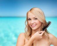 Glimlachende vrouw met haarborstel Royalty-vrije Stock Afbeelding
