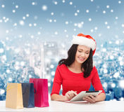 Glimlachende vrouw met het winkelen zakken en tabletpc Royalty-vrije Stock Fotografie