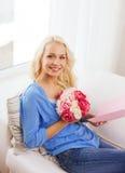 Glimlachende vrouw met kaart en boeket van bloemen royalty-vrije stock foto's