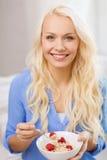 Glimlachende vrouw met kom die van muesli ontbijt hebben stock foto's