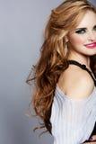 Glimlachende vrouw met lang krullend haar en roze lippenstift royalty-vrije stock foto's
