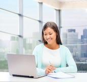 Glimlachende vrouw met laptop en notitieboekje Stock Fotografie