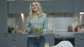 Glimlachende vrouw met salade in keuken stock videobeelden