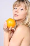 Glimlachende vrouw met sinaasappel Stock Afbeelding