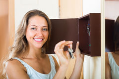 Glimlachende vrouw met sleutel stock afbeelding