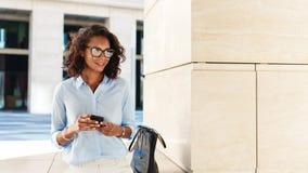 Glimlachende vrouw met smartphone in haar handen stock fotografie