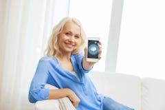 Glimlachende vrouw met smartphone thuis Stock Afbeeldingen
