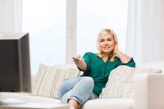 Glimlachende vrouw met verre het letten op TV thuis Stock Fotografie