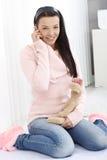 Glimlachende vrouw met zacht stuk speelgoed en mobiel Stock Afbeeldingen