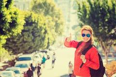 Glimlachende vrouw met zonnebril en rugzak in de stad van San Francisco op zonnige dag Stock Afbeeldingen