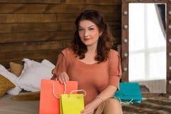Glimlachende vrouw na het winkelen met kleurrijke document zakken op bed Stock Afbeeldingen