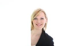 Glimlachende vrouw naast een leeg wit teken Stock Afbeelding