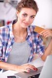 Glimlachende vrouw online het winkelen gebruikende computer en creditcard in keuken Glimlachende Vrouw Stock Foto