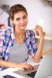 Glimlachende vrouw online het winkelen gebruikende computer en creditcard in keuken Glimlachende Vrouw Stock Fotografie
