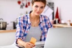 Glimlachende vrouw online het winkelen gebruikende computer en creditcard in keuken Glimlachende Vrouw Stock Afbeeldingen