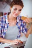 Glimlachende vrouw online het winkelen gebruikende computer en creditcard in keuken Glimlachende Vrouw Stock Foto's