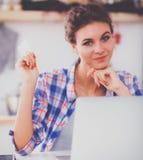 Glimlachende vrouw online het winkelen gebruikende computer en creditcard in keuken Stock Afbeeldingen