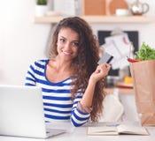 Glimlachende vrouw online het winkelen gebruikende computer en creditcard in keuken Stock Foto