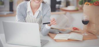 Glimlachende vrouw online het winkelen gebruikende computer en creditcard in keuken Royalty-vrije Stock Afbeeldingen