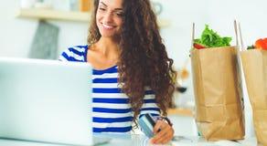 Glimlachende vrouw online het winkelen gebruikende computer en creditcard in keuken Stock Foto's