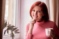 Glimlachende vrouw op middelbare leeftijd met rood haar die zich met witte mok dichtbij venster bevinden Kort koffiepauzeconcept royalty-vrije stock foto